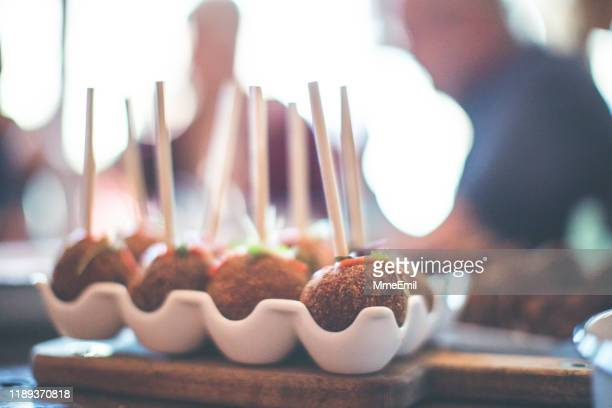 party food, arancini, cake pop style on a buffet table - mmeemil stock photos and pictures