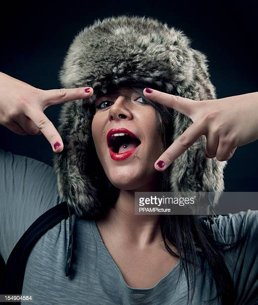 party girl wearing fur hat showing victory sign - fur hat stock photos and pictures