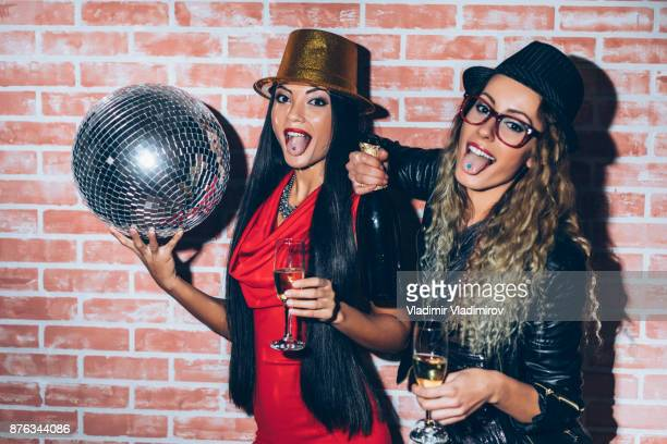 Party girls with disco ball and champagne flutes