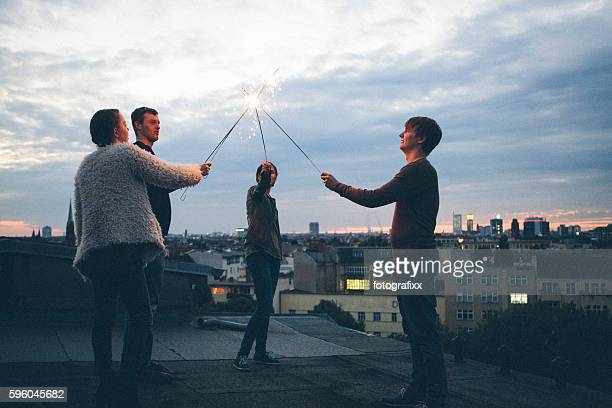 Party: group of young adults standing on roof, holding sparklers