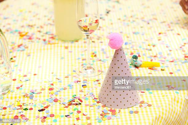 Party hat and party blower on table with confetti