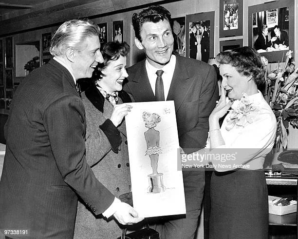 Party host John Bruno offers Shirley Booth an illustration of the Hollywood Oscar which she is hoping to win this year for her 'Come Back Little...