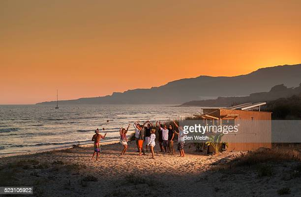 Party in front of beach hut at sunset