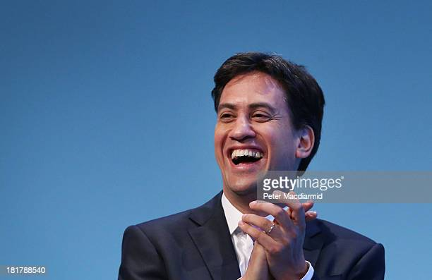 Party leader Ed Miliband laughs during a speech by deputy leader Harriet Harman during the Labour Party conference on September 25 2013 in Brighton...