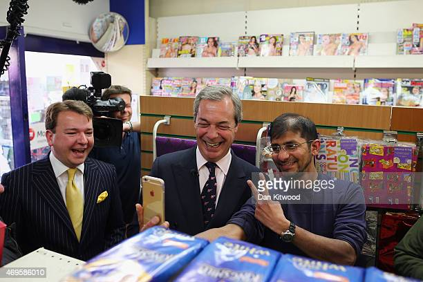 UKIP party leader Nigel Farage poses for a photo with a member of the public as he visits shops on a campaign visit to the high street on April 13...