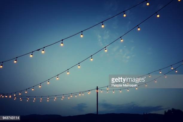 party lights at outdoor wedding reception - verlicht stockfoto's en -beelden