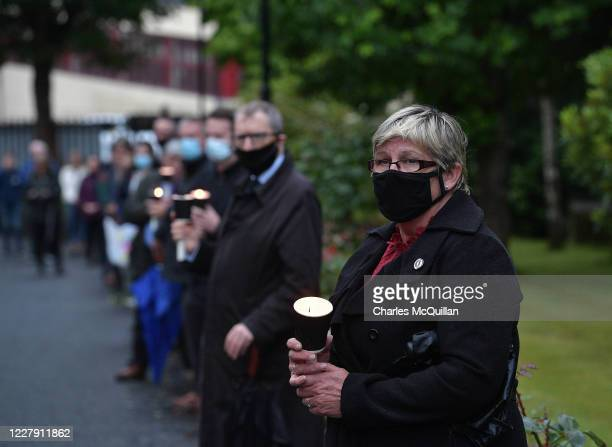 Party members hold candles as they form a guard of honour for former party leader John Hume as his body is brought to St Eugene's Cathedral on August...