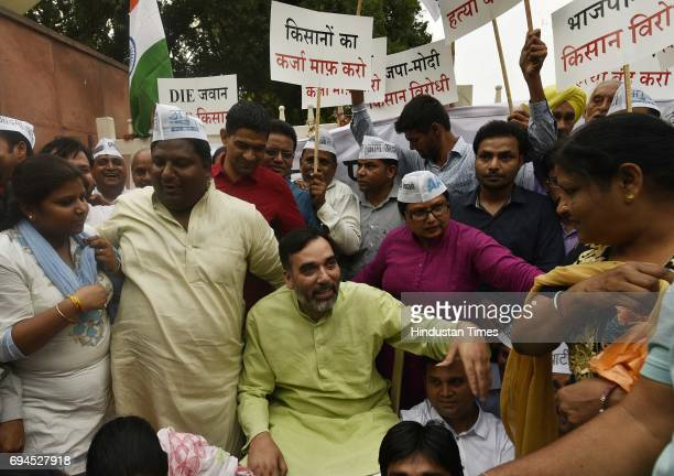 Party Minister Gopal Rai with other party leaders sits in protest against Shivraj Singh's government for police firing on farmers at Kisan Ghat in...