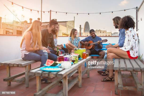 Party of friends around table playing music at dusk