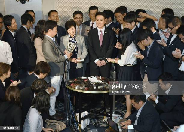 Party of Hope leader Yuriko Koike alongside Democratic Party leader Seiji Maehara speaks to reporters in Tokyo on Oct 5 2017 Koike reiterated that...
