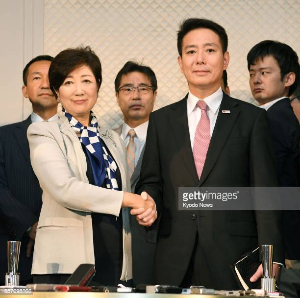 Party of Hope leader Yuriko Koike alongside Democratic Party leader Seiji Maehara shake hands in front of reporters in Tokyo on Oct 5 2017 Koike...