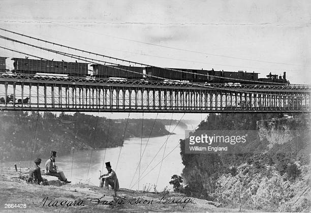 A party of men sit on the Niagara cliffs as a steam train and a horse and carriage cross the river on the twotier suspension bridge Built in 1855 by...