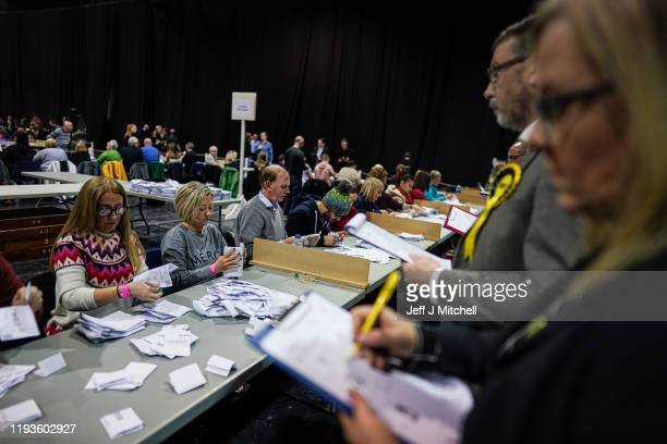 A party official observes as counting staff count ballots at the main Glasgow counting centre in the SECC on December 12 2019 in Glasgow Scotland The...