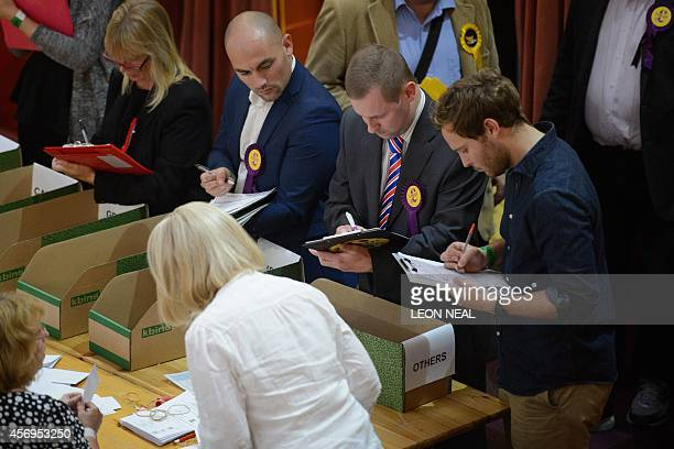 Party officials watch as count centre staff verify ballot papers at the ClactonOnSea byelection ballot count in eastern England on October 9 2014 A...