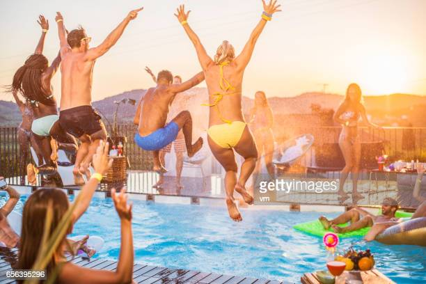 party people jumping in the pool - pool party stock pictures, royalty-free photos & images
