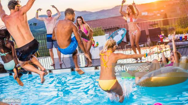 Party people jumping in the pool