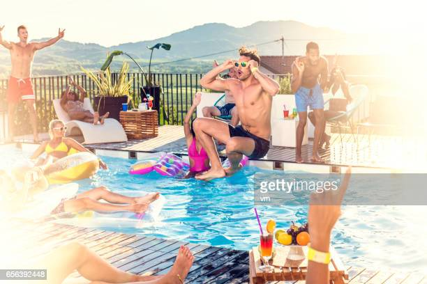 Party people jumping into pool