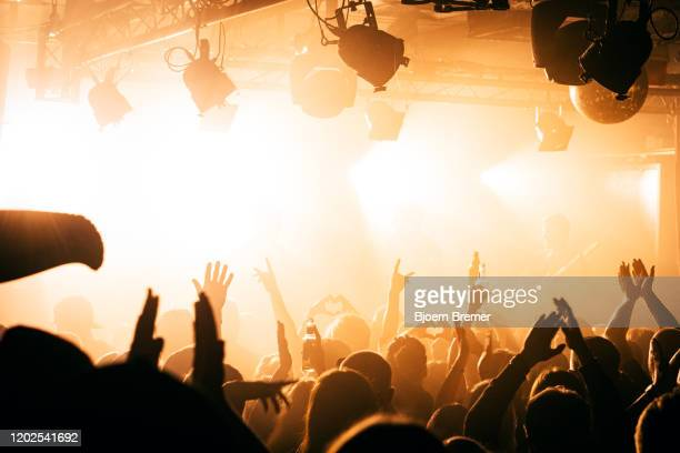party people waving their hands at a party in a club - diskothek stock-fotos und bilder