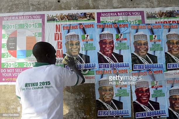 A party supporter cleans poster of the opposition All Progressives Congress presidential aspirant Atiku Abubakar within the presidential primary of...