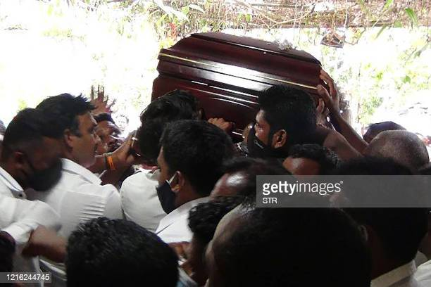 Party supporters breaching social distancing rules carry the coffin of Arumugam Thondaman leader of a tea plantation union and a minister in the...