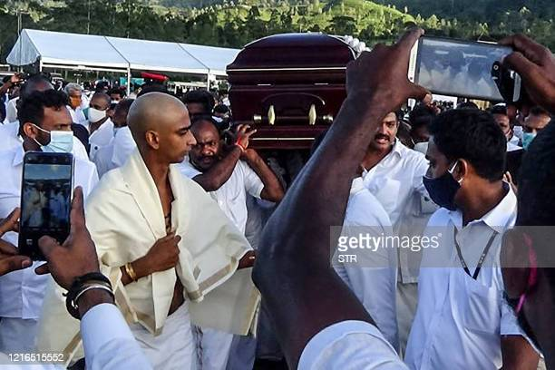 Party supporters carry the coffin of late tea plantation trade union leader and government minister Arumugam Thondaman in the central city of Norwood...