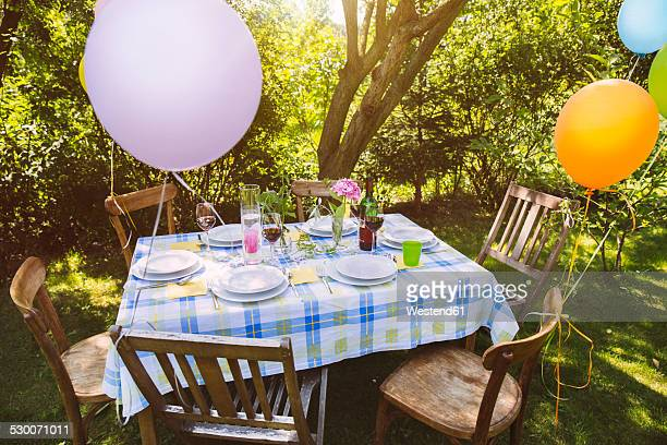 Party table in garden with plates and glasses