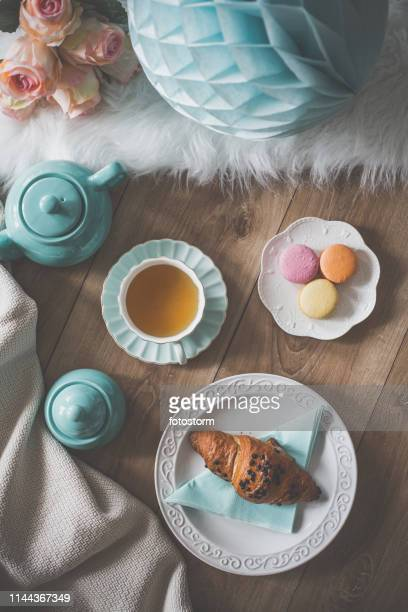 Party table with macaroons, tea and croissant