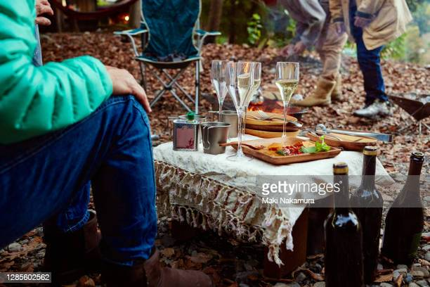 party tableware is placed on a small table on the ground covered with dead leaves. - 自然 ストックフォトと画像