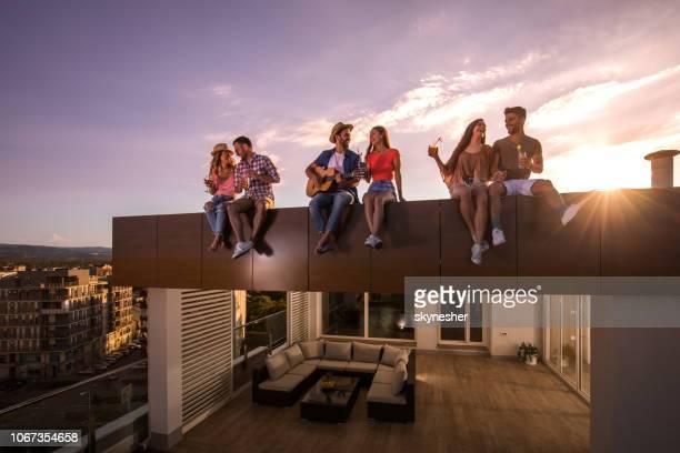 ¡fiesta con una guitarra en una terraza al atardecer! - stringed instrument fotografías e imágenes de stock