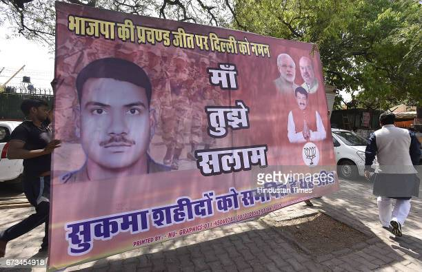 BJP party workers stick poster of the CRPF jawans martyred in Sukma at Delhi Pant Marg BJP Office on April 26 2017 in New Delhi India It's a third...
