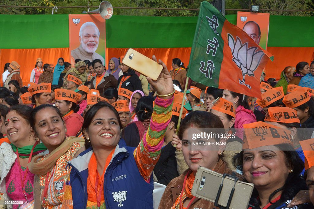 Party workers take selfie photographs during the Bharatiya Janata Party rally at the PAP ground in Jalandhar on January 27 2017 / AFP / Narinder NANU