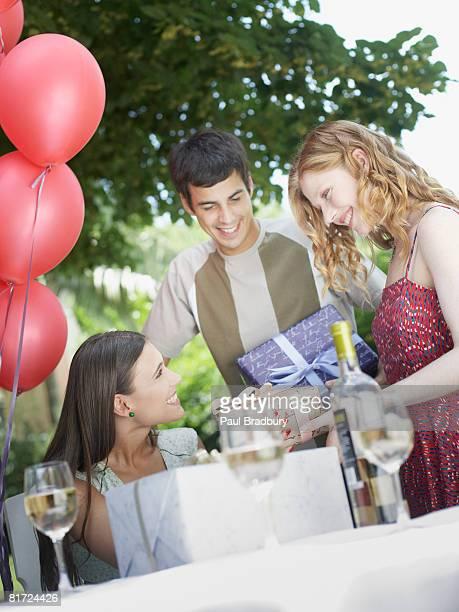 姿での屋外パーティに贈り物をすると笑顔の女性