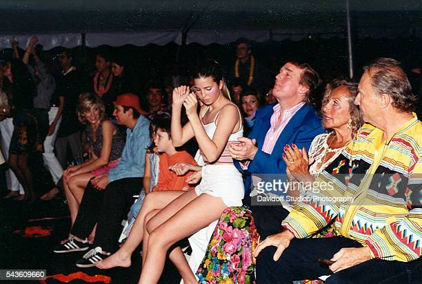 Partygoers including Ivanka Trump who her sits on her father businessman Donald Trump's lap during concert at the MaraLago estate Palm Beach Florida...