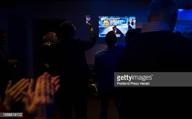 Partygoers record as CNN announces that Democrats took the House of Representatives at the Maine Democrats election night party for gubernatorial...