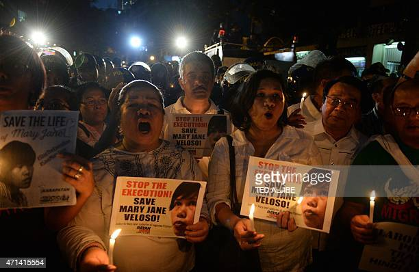 Partylist legislators Carlos Zarate and Neri Colmenares and other activists holding candles and placards with portraits of Filipina Mary Jane Veloso...