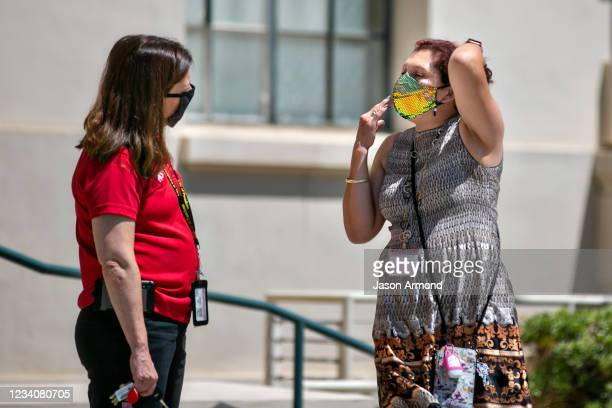 Pasadena city employee points towards her face mask as she talks with a fellow city employee on the steps of City Hall on Tuesday, July 20, 2021 in...
