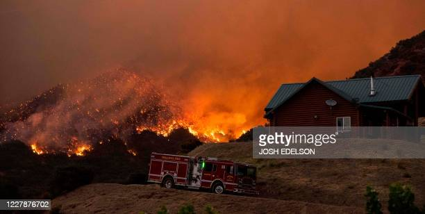 Pasadena Fire Department firefighters perform structure protection as flames sparkle on a hillside behind a home during the Apple fire in Banning,...