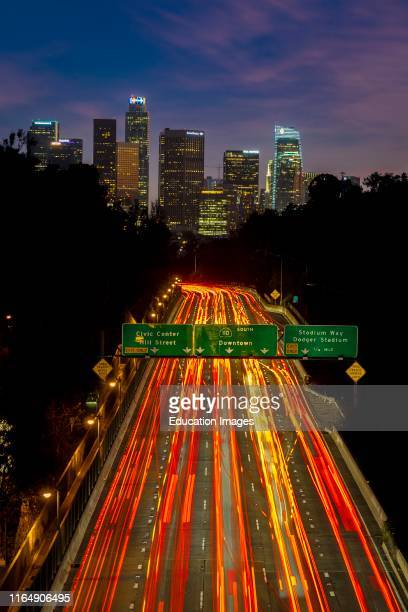 Pasadena Freeway, Arroyo Seco Parkway, CA 110 leads to downtown Los Angeles with streaked car lights at sunset.