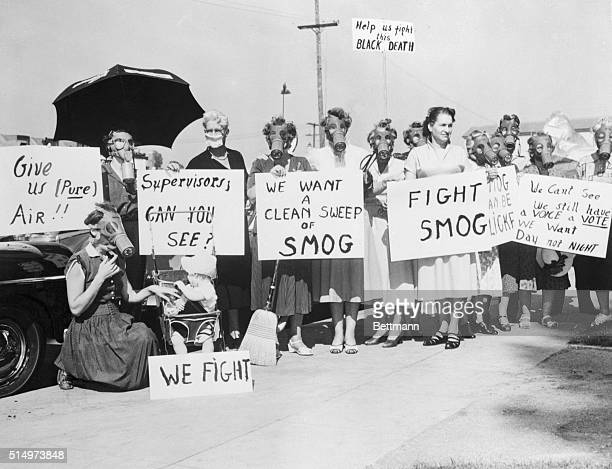 Pasadena housewives wear gas masks and carry signs protesting the smog which has plagued them for the last 15 days as they parade before the Pasadena...