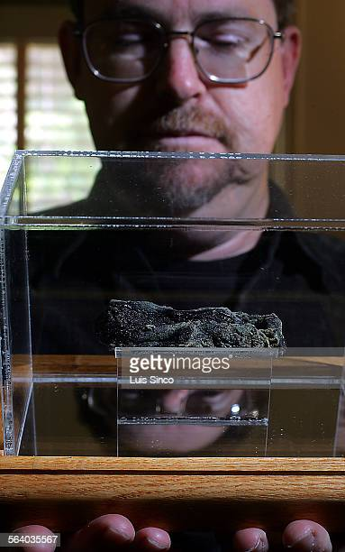 Pasadena resident Terry Cannon holds a glass case containing the moldy remains of a hot dog that was partially eaten by baseball legend Babe Ruth The...