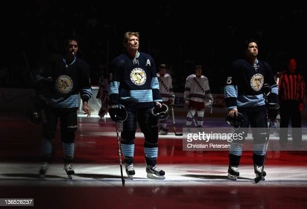 Pascal Dupuis Jordan Staal and Deryk Engelland of the Pittsburgh Penguins stand attended for the National Anthem before the NHL game against the New...