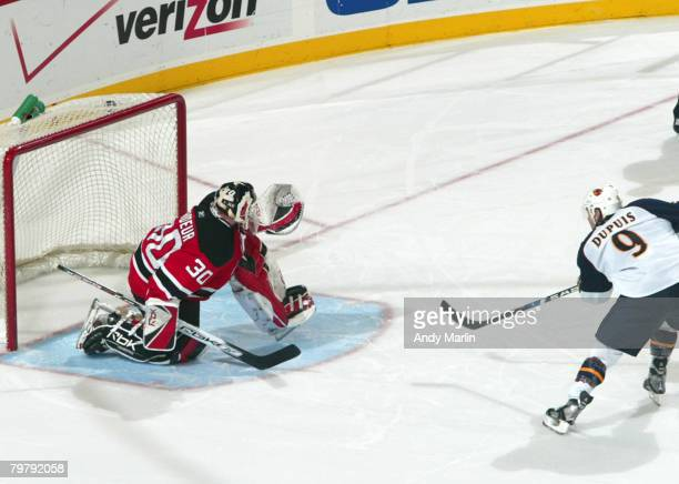 Pascal Dupuis of the Atlanta Thrashers roofs the puck for the deciding goal in the shootout against Martin Brodeur of the New Jersey Devils during...