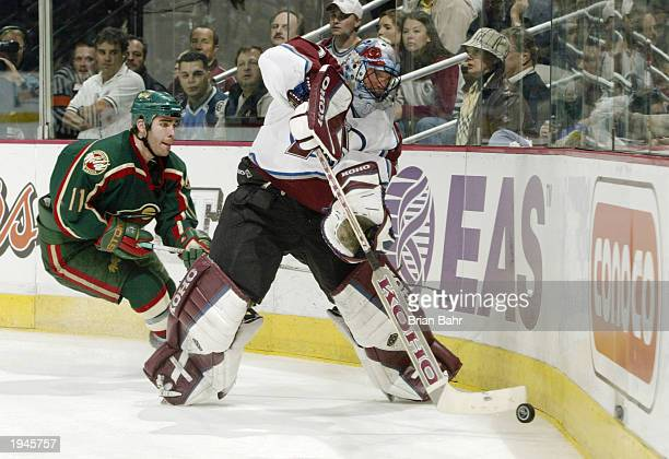 Pascal Dupuis of the Minnesota Wild pressures goalie Patrick Roy of the Colorado Avalanche as he clears the puck in the second period during game...