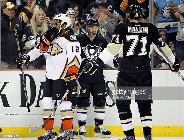 Pascal Dupuis of the Pittsburgh Penguins celebrates his first period goal with Evgeni Malkin against the Anaheim Ducks during the season opener at...