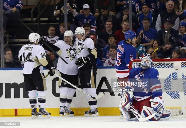 Pascal Dupuis of the Pittsburgh Penguins scores a second period goal against Henrik Lundqvist of the New York Rangers and is joined by Chris Kunitz...