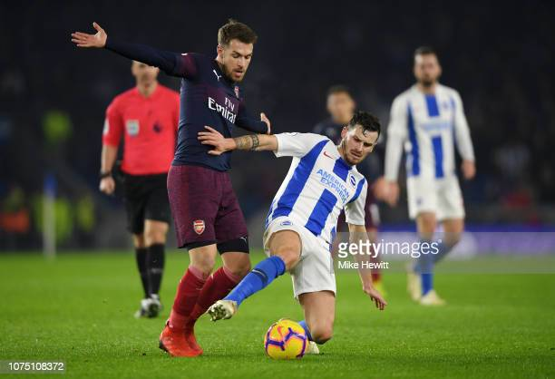 Pascal Gross of Brighton Hove Albion is challenged by Aaron Ramsey of Arsenal during the Premier League match between Brighton Hove Albion and...