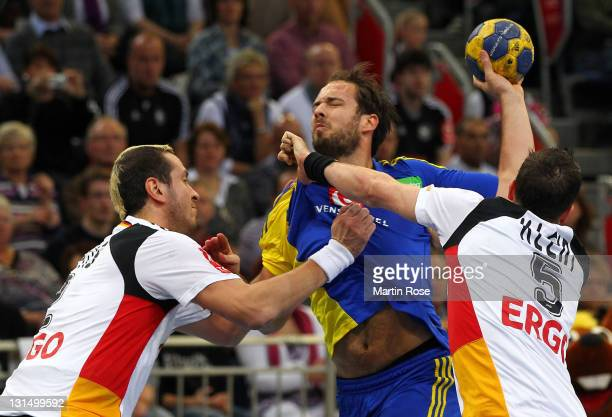 Pascal Hens and Dominik Klein of Germany and Lukas Karlsson of Sweden compete for the ball during the Men's Handball Supercup match between Germany...