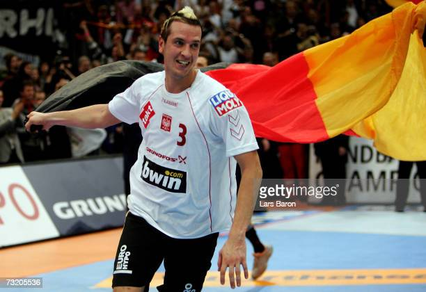 Pascal Hens celebrates with a german flag after winning the IHF World Championship final game between Germany and Poland at the Cologne Arena on...
