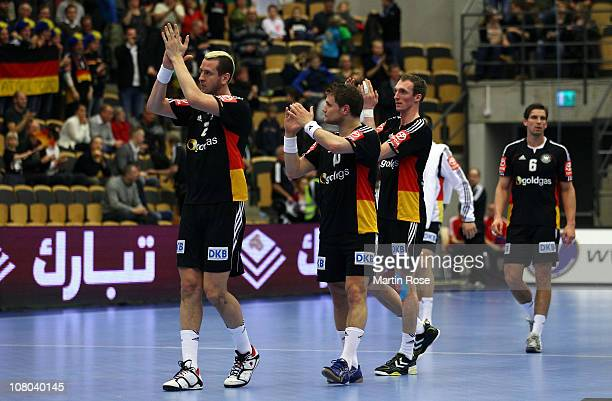 Pascal Hens, Michael Krauso and Holger Glandord of Germany celebrate after winning the Men's Handball World Championship Group A match between...