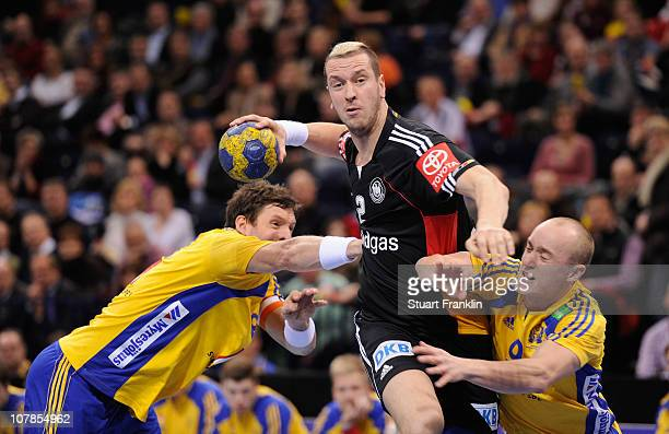 Pascal Hens of Germany is challenged by Jan Lennartsson and Tobias Karlsson of Sweden during the international friendly handball match between...